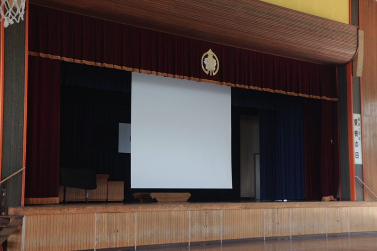 小学校体育館ステージに幅4mの遠距離操作電動ケース付きスクリーンを導入いただきました!