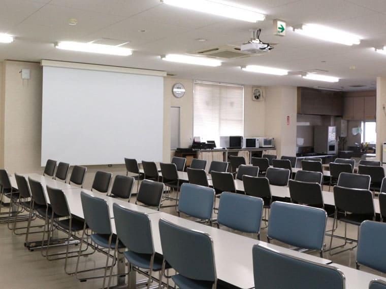 会社の食堂に120インチのスクリーンを導入して全体朝礼やミーティングに活用